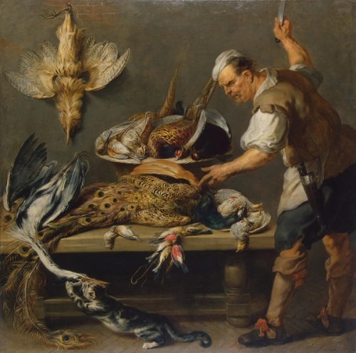 A cook standing by a tab;e cutting up game birds while a cat attempts to steal one.