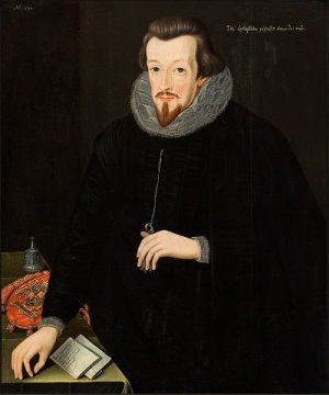 A thin-faced, bearded man in dark clothes, with papers and an official red, embroidered, dispatch bag beside him.