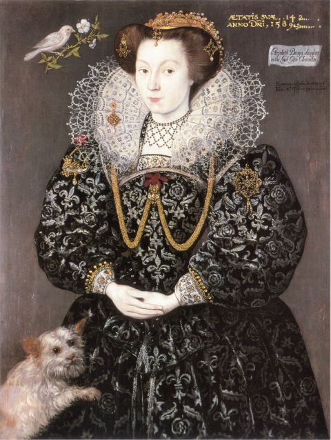 An elaborately dressed Elizabethan girls posed with a small dog.