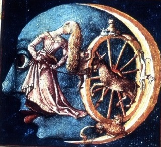 A woman whose face is hidden by her long hair turns a wheel with various animals on it; a monkey, dogs, a large spotted cat, and a donkey. Set against the background of a moon with human facial features.