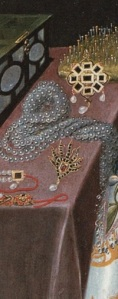 A detail from an early portrait of Elizabeth Vernon, showing an open jewellery box, a lavish display of pearls, brooches etc, and a pincushion containing the pins grand Elizabethan ladies used to hold their formal attire together.