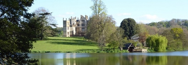 A late Elizabethan grey stone house, surrounded by parkland.