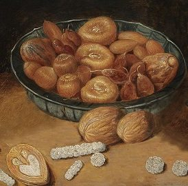 A bowl containing dried figs, candied fruit and nuts, with sweets made from white sugar lying on the table.