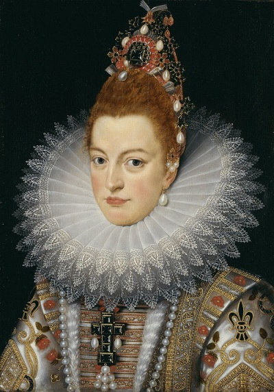 An attractive young woman with high-piled reddish hair, and a hint of the long Habsburg chin. She is richly dressed and jewelled.