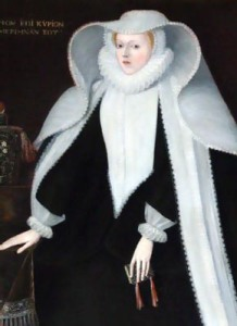A fair, delicate-featured woman in a black gown with a white ruff and a voluminous white head-dress.