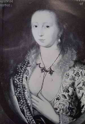 An upper body portrait of young woman with a thoughtful expression wearing her hair loose. She's informally dressed in a robe with a low neckline.