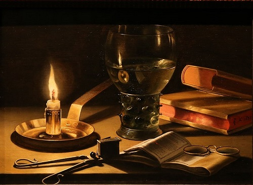 A lit candle, candle-snuffer, glass of wine and books on a table.